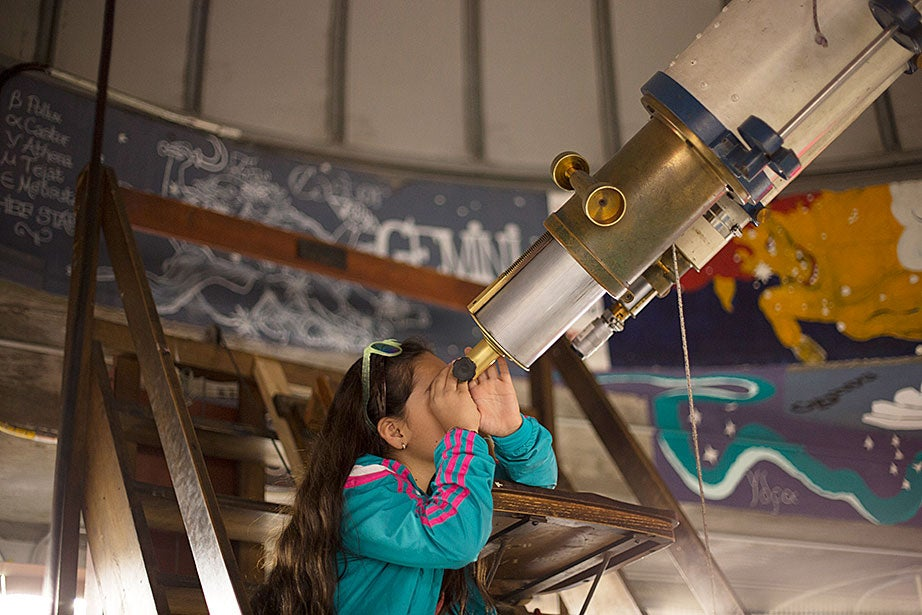 Nine-year-old Livis Gonzalez looks at Jupiter through the Loomis-Michael telescope while visiting Harvard with her parents.