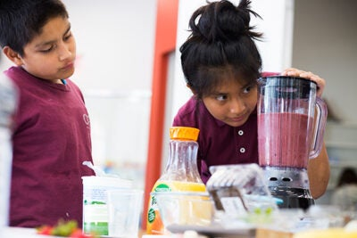 "Luis Agulion (left) and Jennifer Mauricio keep an eye on their latest science project at the Harvard Ed Portal's ""Science and Cooking for Kids"" program."