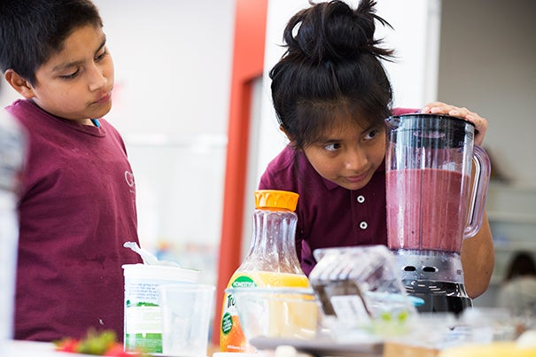 """Luis Agulion (left) and Jennifer Mauricio keep an eye on their latest science project at the Harvard Ed Portal's """"Science and Cooking for Kids"""" program."""