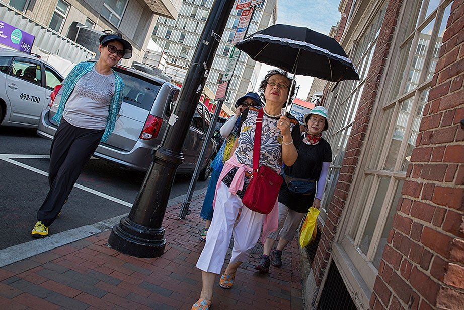 Tourists from South Korea stay shaded on Holyoke Street.