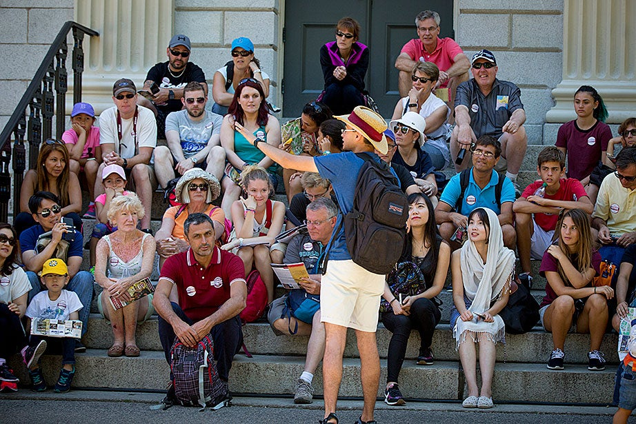 A group meets on the steps of University Hall.