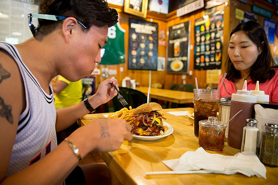Dealing Moon of South Korea, visiting with his wife, Seonyoung, had trouble finishing his first hamburger — a triple decker at Bartley's on Mass. Ave., and needed a fork and knife.