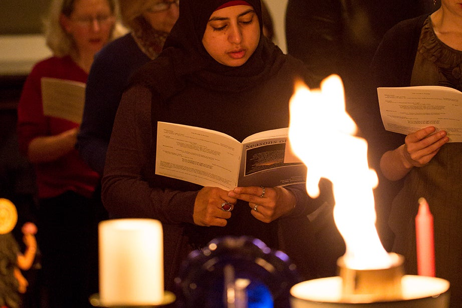 At the 2013 Seasons of Light celebration in Andover Chapel, students from 11 religious groups each lit a candle or candles in recognition of their tradition's winter celebration. Usra Ghazi, M.T.S. '15, who lit a candle for the Muslim faith, is seen behind the flaming chalice, the symbol of the Unitarian Universalist Association. Photo by Brian Tortora/HDS