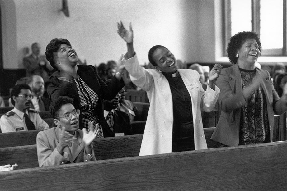 A service in Andover Hall marking Black History Month. Delores Lovett-Sconiers, M.Div. '91 (center), and Natalie P. Alford, M.Div. '92 (right), worship in Andover Chapel. Four guest preachers spoke at weekly services during Black History Month in 1991. Among them were two fathers of students, the Rev. Hycel B. Taylor (father of Chandra Taylor Smith, M.Div. '88) and the Rev. Howard Fauntroy Jr., B.Div. '66 (father of Howard Fauntroy III, M.Div. '93), and the Rev. Frank M. Reid, M.Div. '78. Dean Ronald Thiemann sponsored the program and is visible in a back pew. Photo by Bradford Herzog/HDS