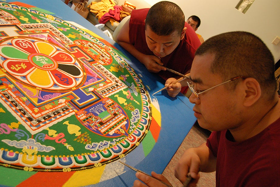 Three mandalas have been created at the CSWR over the past 15 years. In 2008, Geshe Kalsang and Venerable Phuntsok from the Gaden Shartse Monastery sifted colored sand to create a mandala of compassion, named for Chenrezig, who pledged not to attain Buddhahood until all sentient beings were free from the sufferings of samsara. In keeping with tradition, each sand painting, once complete, is swept away in a communal ceremony to demonstrate the impermanence of all things. At an audiovisual station, Janet Gyatso narrates the creation of the Wheel of Life mandala in 2005 for the 45th anniversary of the CSWR. Photo by Kristie Welsh/HDS