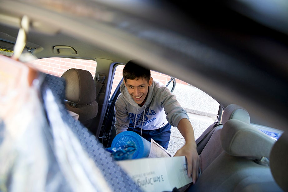 """Unpacking his parents' car in Harvard Yard, Will Quan of Somerville, Mass., said, """"It hasn't set in yet — I'm excited to see what's next. I've been in the area a long time, but this is a different feeling."""" Rose Lincoln/Harvard Staff Photographer"""