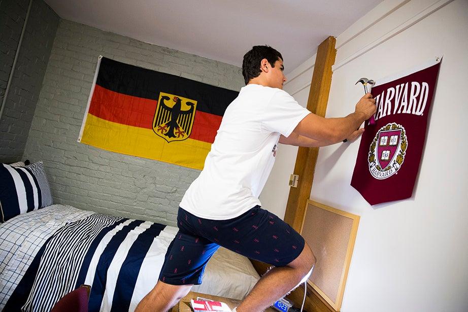 Kyle Bierdumpfel '20 hangs a Harvard flag alongside a German flag. Bierdumpfel, a wrestler from North Jersey, will be studying German at Harvard. Stephanie Mitchell/Harvard Staff Photographer