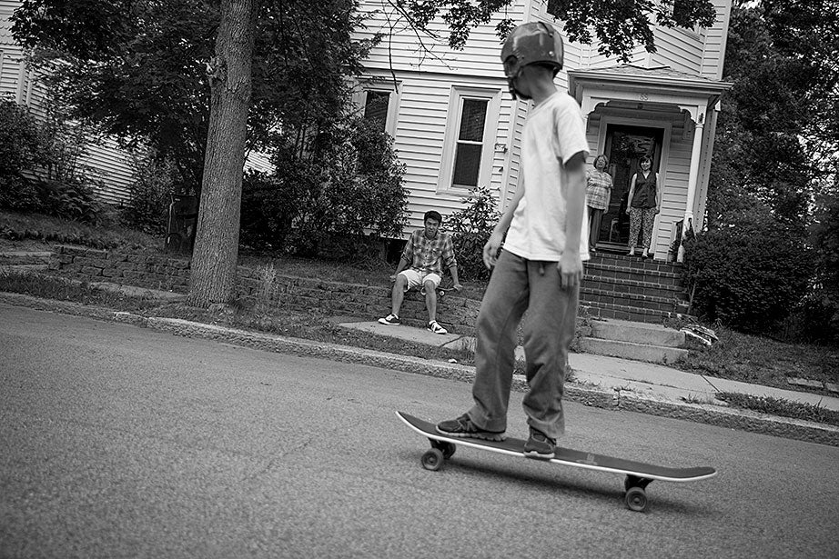 Neil takes Kevin's longboard for a ride in their neighborhood.