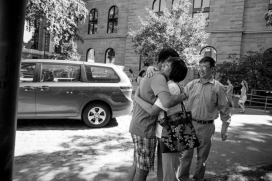 """Kevin hugs his mother. His father, Hailin, said he would miss work to be at move-in day partly so he could, """"park the car in Harvard Yard."""" The family car is to the left."""