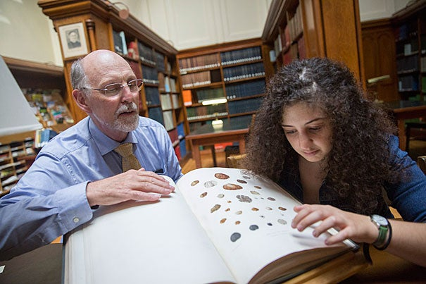 Inside the Harvard University Herbaria's Farlow Library, Professor Don Pfister (left) and Hannah Zurier '17 discuss a recently published article about her work discovering a new truffle fungus at the Arnold Arboretum.