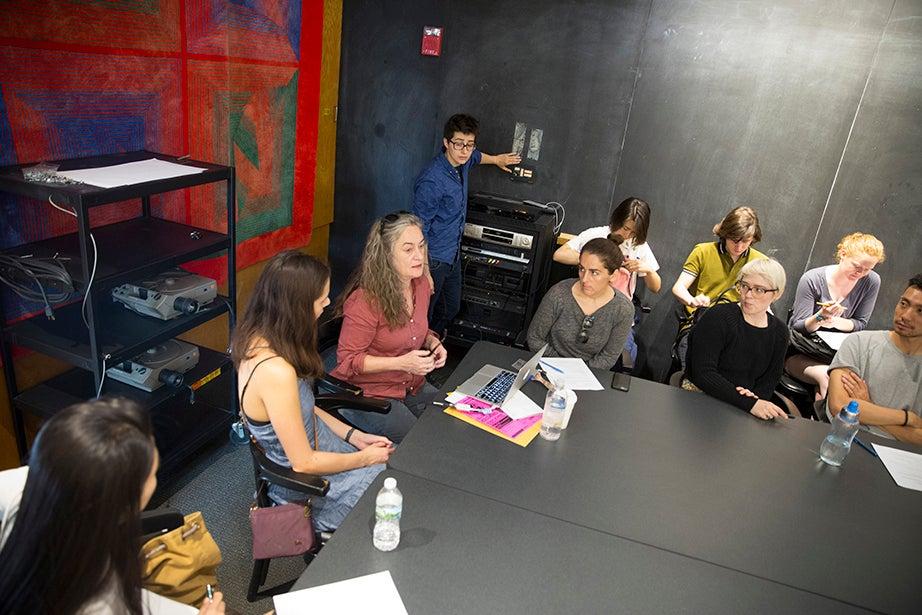 "Teaching fellow Amelia Spinney (standing) operates the slideshow in Annette Lemieux's (center) ""Silkscreen"" class. Kris Snibbe/Harvard Staff Photographer"
