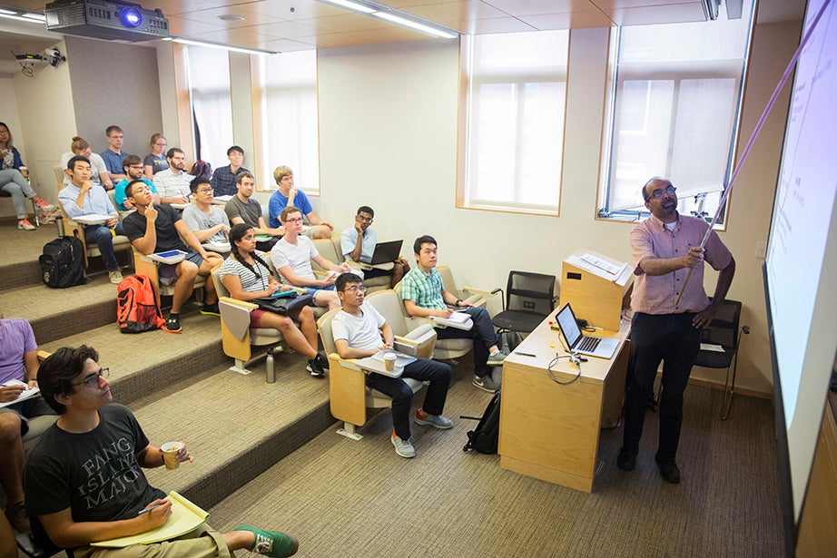 """L. Mahadevan teaches """"Fluid Dynamics"""" in the Cruft Building. The course explores continuum mechanics; conservation of mass and momentum; energy, stress, kinematics, and constitutive equations; vector and tensor calculus; and dimensional analysis and scaling. Kris Snibbe/Harvard Staff Photographer"""