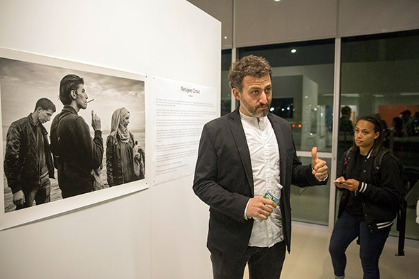 """Maciek Nabrdalik (left)  Nieman Fellow and documentary photographer, speaks about his exhibit, """"Refugee Crisis,"""" at the Crossings Gallery at the Harvard EdPortal. """"I don't treat it as artwork. It's not a show that I would like you to ... compliment me for."""""""
