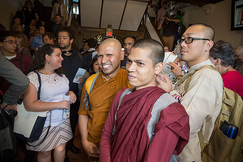 "Across the street from the Center for the Study of World Religions at Andover Hall, HDS students Kusala Bhante (from left), a Buddhist monk from Sri Lanka; former CSWR resident Priya Rakkhit, Sraman, a Buddhist monk from Bangladesh; and Hyun Shin, a Korean Buddhist monk, attend a reception for the ""Faces of Divinity"" exhibition at the Divinity School bicentennial."