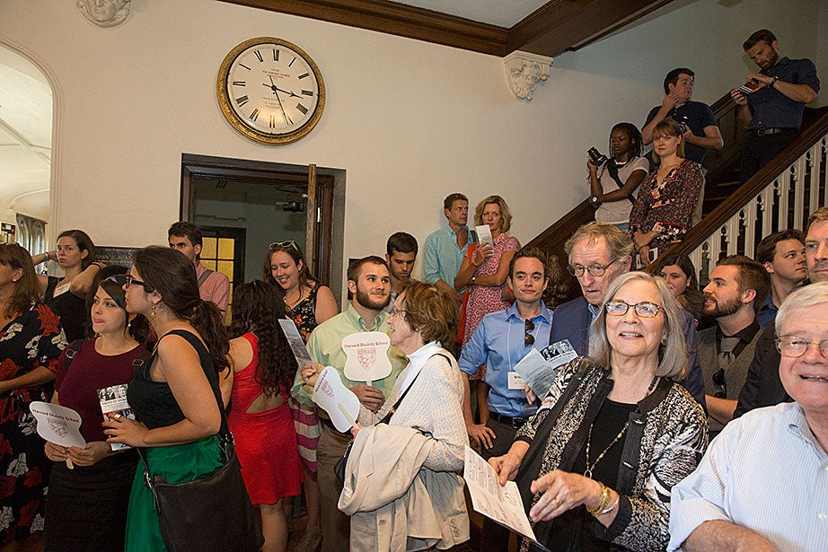 "HDS student Daniel Kraft (center, beard and green shirt) attends a reception for the ""Faces of Divinity"" exhibition. ""I have been privileged to participate in so many interesting and stimulating colloquia and lectures, meet so many visitors, including former residents over nearly six decades, and to help convene so many conversations essential to the good health of the study of religions at the Divinity School, at Harvard, in today's religiously diverse and ever-changing world,"" said CSWR director Francis Clooney."
