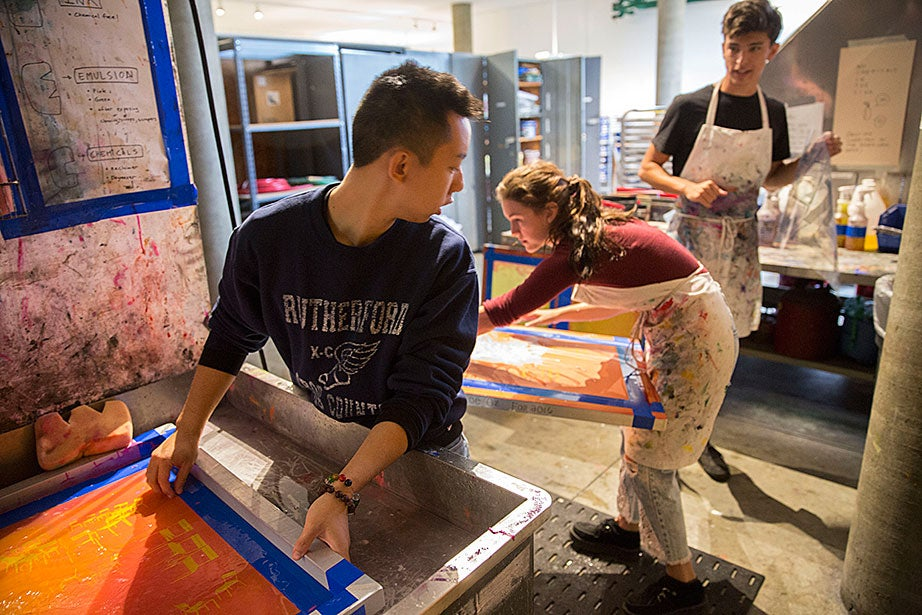 James Jacoby '19 (right) carries a drawing on acetate into the darkroom to create a new silkscreen frame, while Chris Chow '20, (left) and Zoe Oz '17 share sink space together.
