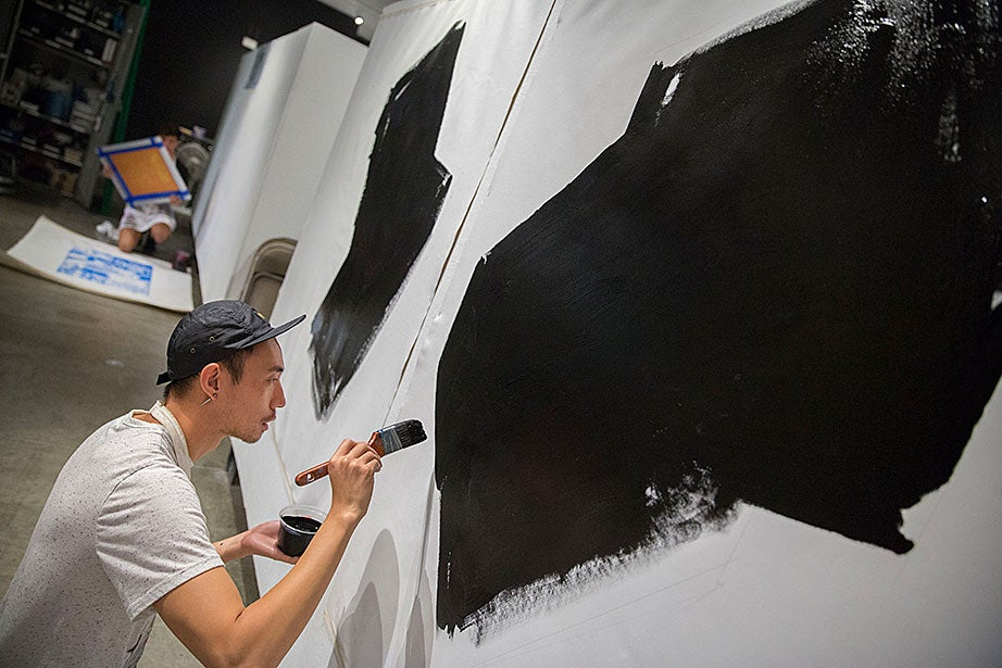 Justin Jiang, GSD student, applies generous amounts of black acrylic paint to his abstract painting during Lemieux's class.