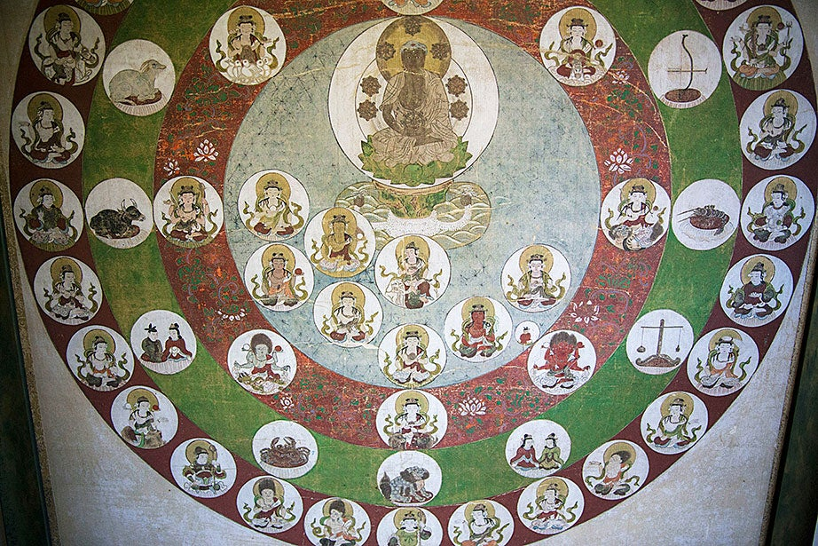"""Shakyamuni Buddha Surrounded by Heavenly Circles,"" a 17th-century mandala of gouache and ink on silk, is displayed in the CSWR common room."