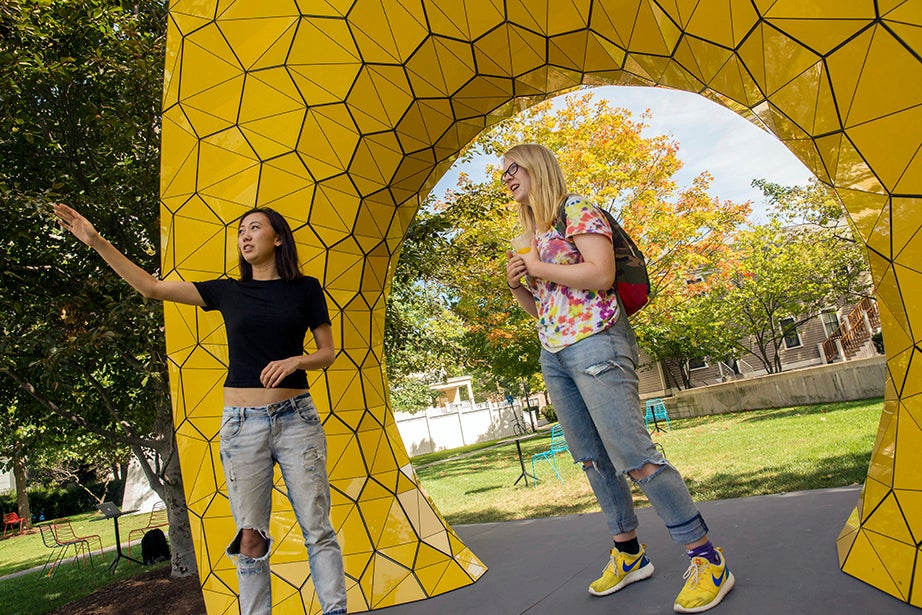 """Diana Yan, GSD '18 (left), and Susie Clements '19 pose with the art installation """"Grid Structure"""" outside Gund Hall at Harvard Graduate School of Design. Kris Snibbe/Harvard Staff Photographer"""