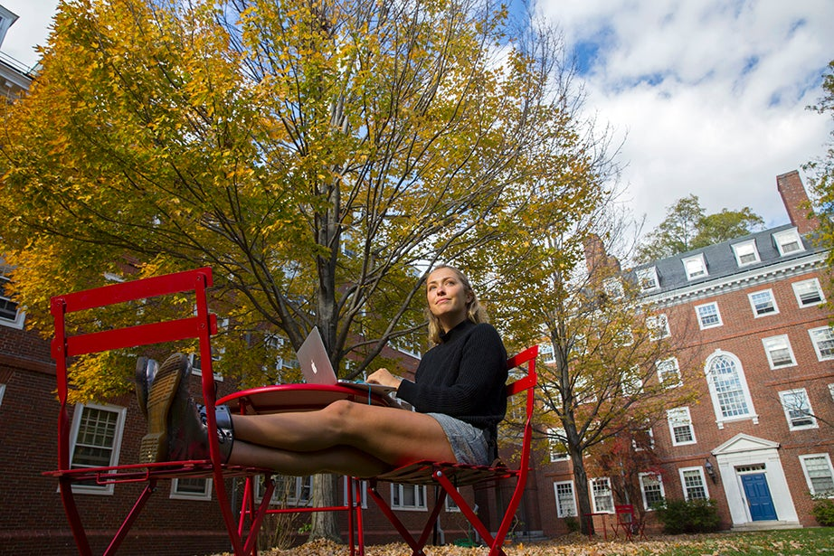 Amid a glow of autumn color, Katie Tutrone '17 studies in the Lowell House courtyard. Kris Snibbe/Harvard Staff Photographer
