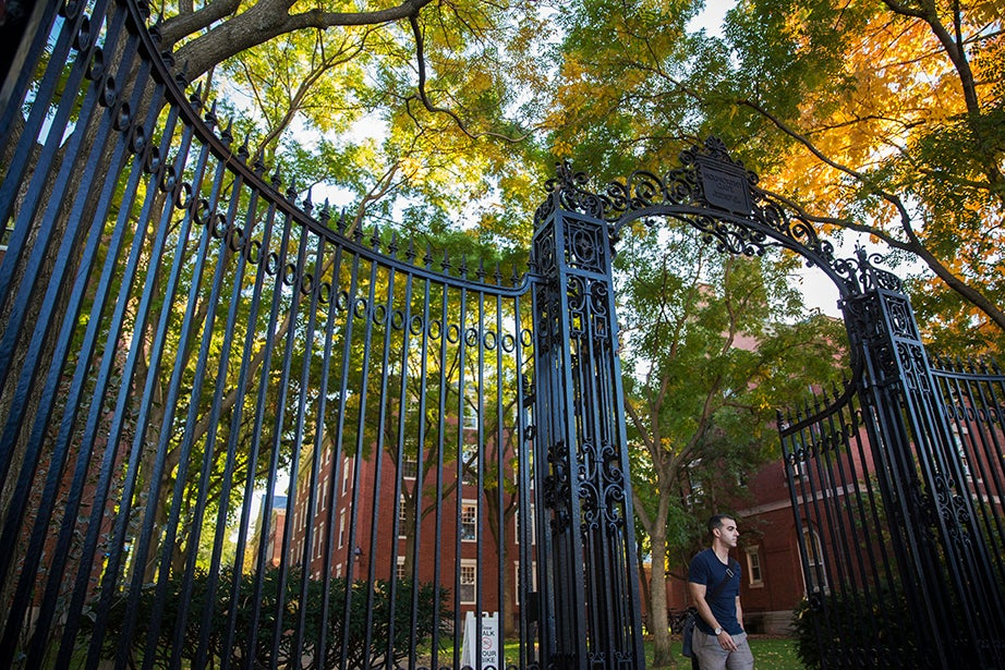 """Foliage frames the Holworthy Gate, inscribed """"In Memory of Dear Old Times."""" Kris Snibbe/Harvard Staff Photographer"""