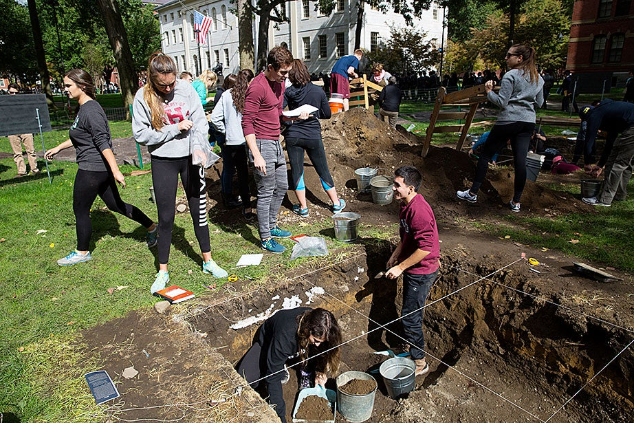 """Students in """"Anthropology 1130: The Archaeology of Harvard Yard"""" dig in rectangular pits, inside areas sectioned off by twine, a few centimeters at a time. The class excavates in partnership with the Peabody Museum of Archaeology and Ethnology."""