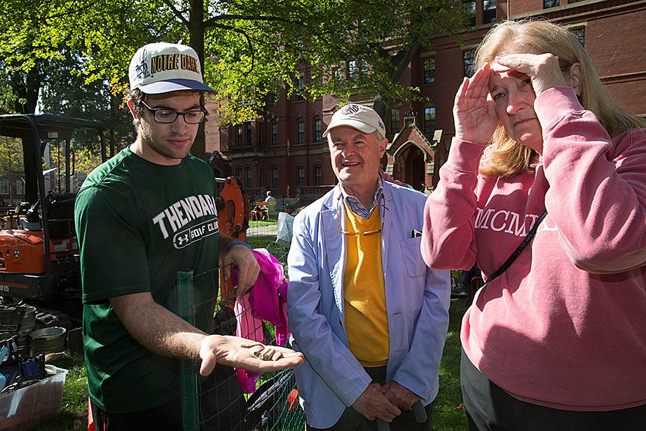 Colin Criss '17, left, displays some recently excavated artifacts to Tom Tiffany '71, center, and Meryl Strawbridge '71.