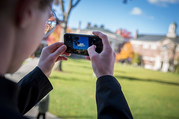 """Jasper Johnston '20, creator of the Instagram photography project """"100 Days of Harvard,"""" snaps a photo from the steps of Longfellow Hall in Radcliffe Yard."""