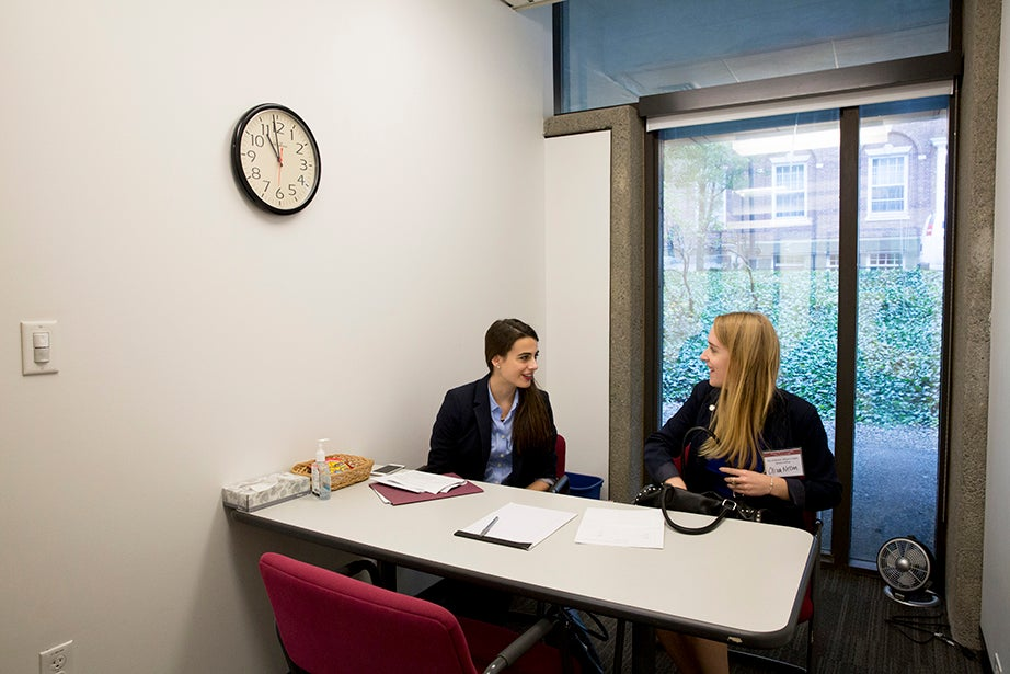 Lender and Nelson wait for their first interviewee. A Harvard senior will replace Lender when her year is completed next fall.