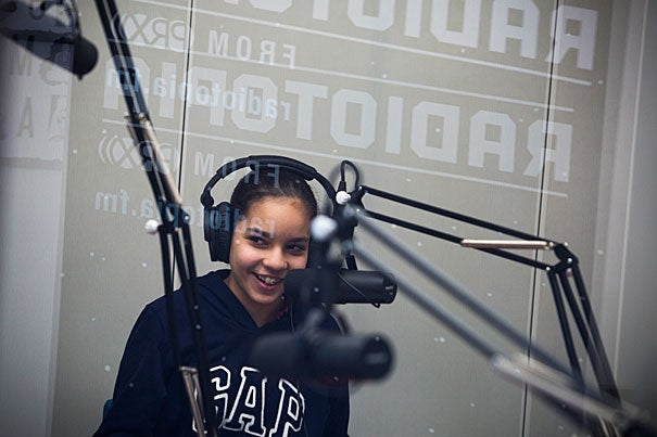 Gardner Pilot Academy sixth-grader Michelle Mota reads her story in the recording booth at the PRX Podcast Garage in Allston, where her class put together memoirs.