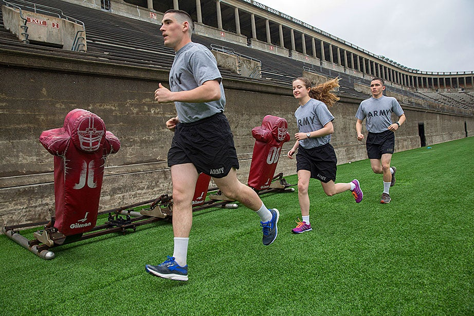 "Framed by football training equipment, Luke Pumiglia '17 (from left), Alannah O'Brien '19, and Nathan Williams '18 run together at the Harvard Stadium. ""I joined Army ROTC in order to help shape future military policy,"" said Williams, ""Through Army ROTC, I've entered a tight-knit community of cadets who not just push one another to their physical limits, but also never hesitate to help one another during times of need."""