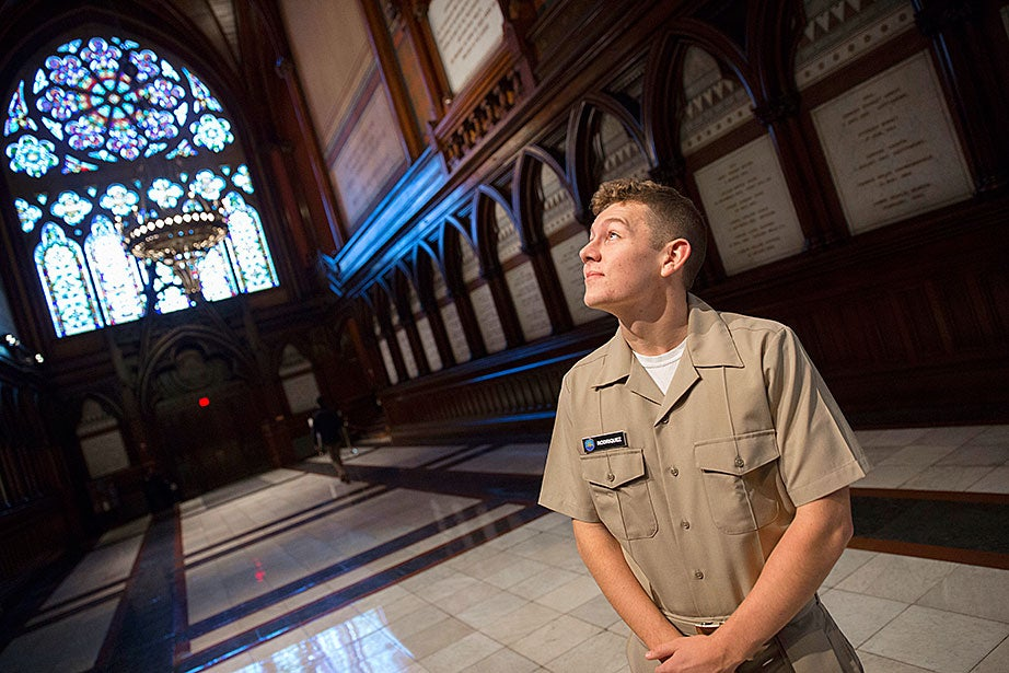 Lit by stained-glass windows, Brendan Rodriguez '20 admires the display of military history inside the Memorial Hall.