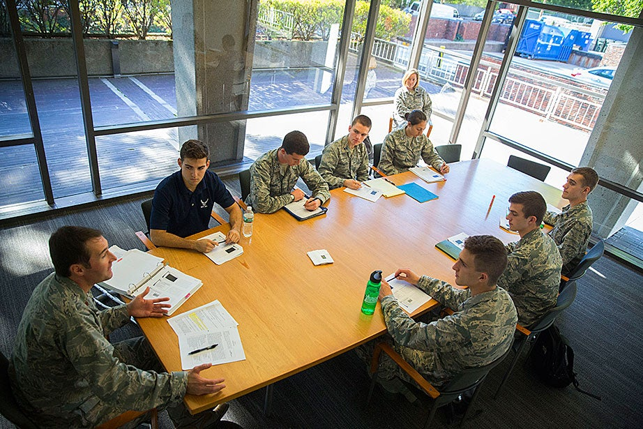 U.S. Air Force Maj. Michael Clifford (clockwise from far left), an assistant professor in aerospace studies at MIT, teaches cadets Ryan Comrie '19, Peter Hartnett '19, both from Harvard; Ryan Friedman '19, from Tufts; Jordanne Stobbs-Vergara '19, of Wellesley; and MIT students Matthew Hutchinson '19, Riley Steindl '19, Alexander Knapp '19, during Air Force ROTC academic classes and Leadership Laboratory inside the Harvard Student Organization Center at Hillis. Commander Sheryl Double Ott of the Air Force ROTC Detachment 365, a visiting professor at MIT (upper right), looks on.