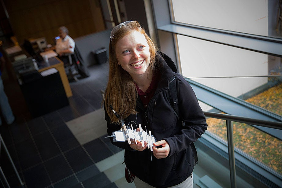After attending a science class at 60 Oxford St., Kira Headrick '17, holds a prototype of her senior thesis project — a variable stiffness paper folding mechanism that will be used for a soft silicone rubber robotic leg.