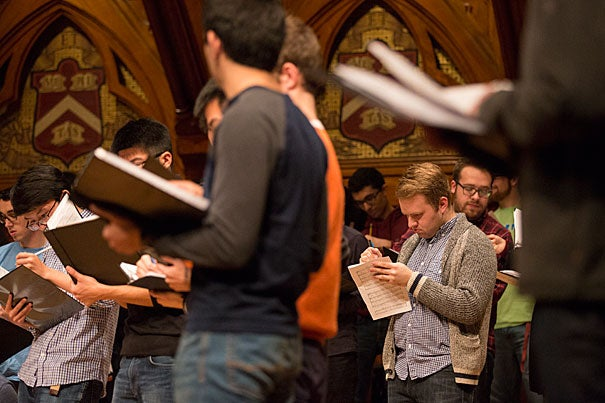 Harvard Glee Club member Billy Gardner takes notes on his sheet music during a rehearsal for the upcoming Holiday Concert in Sanders Theatre Nov. 30. Photo by Sarah Silbiger