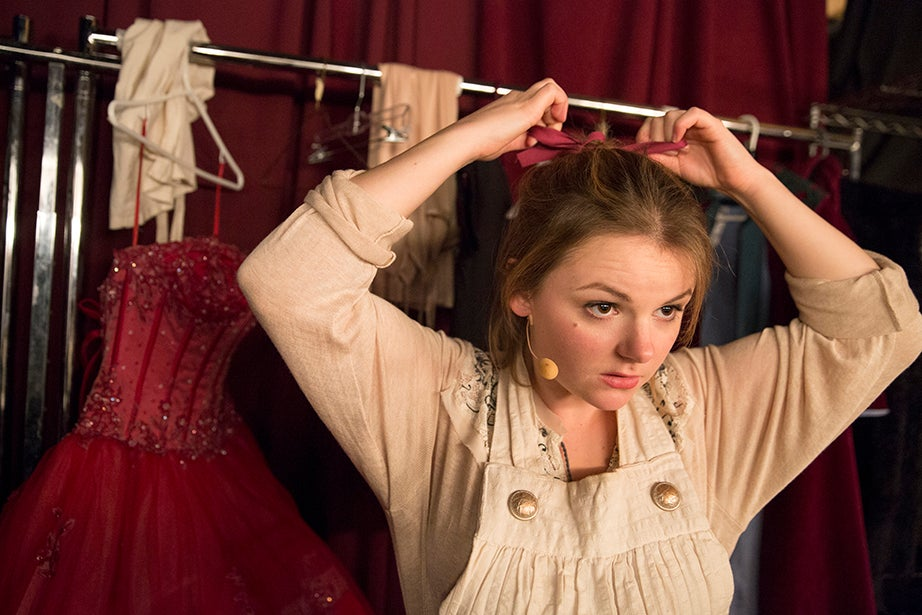 """Eliza Mantz, who plays the Baker's Wife, puts the final touches on her costume, adjusting her hair bow in a nearly empty dressing room before running on stage for the final dress rehearsal of Harvard-Radcliffe's production of """"Into the Woods."""""""