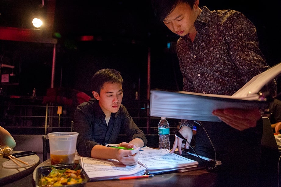 Music Director Brian Ge delivers notes to the orchestra's French horn player during a break. Ge, along with several members of the orchestra, enjoyed a dinner of Chinese take-out in the theater before the cast arrived.