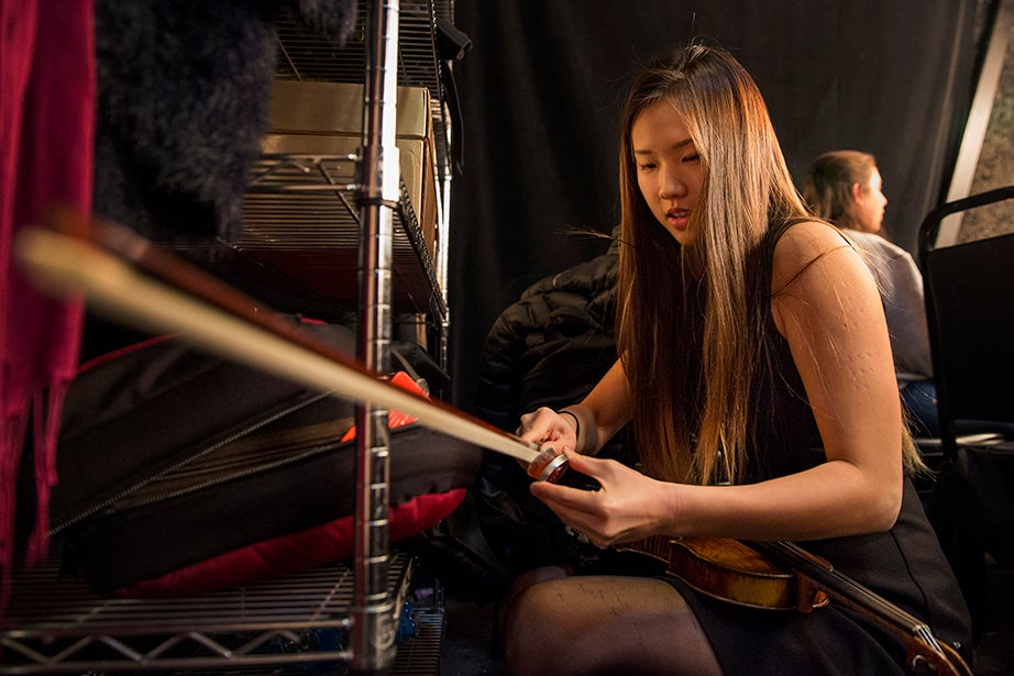 Violinist Christine Hong of the Harvard Chan School of Public Health adds rosin to her bow in the women's dressing room in preparation for her part in the all-student orchestra.