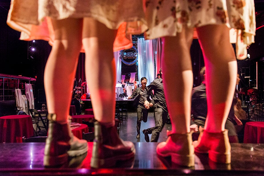 Eliza Mantz and Arianna Paz stand on the Oberon Theater bar as members of the orchestra run out during the performance.
