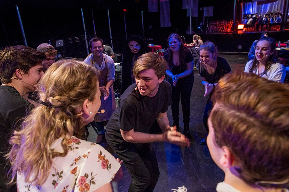 Cole Edick, who plays the Narrator, leads the cast in a cheer to reinvigorate them for the second act.