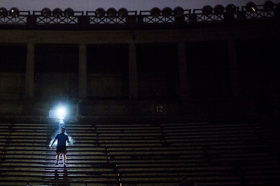 6 a.m. — A member of the 5:30 a.m. November Project group is illuminated by a fellow runner's headlamp as he scales the stone steps of Harvard Stadium. He is one of hundreds of people who gather in the stadium every Wednesday morning, regardless of the month.