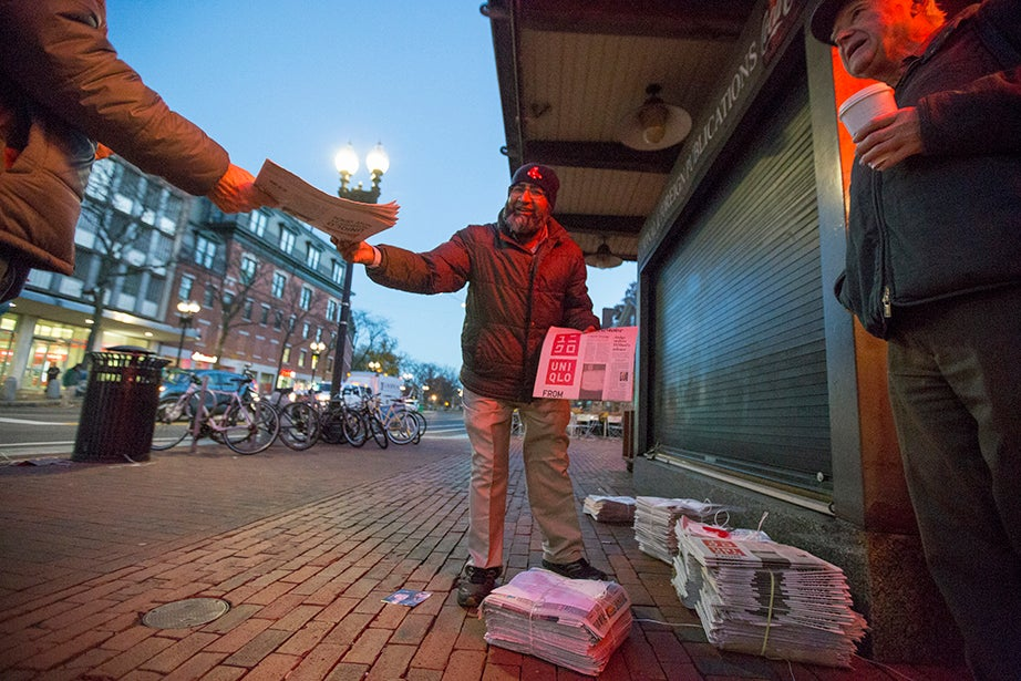 6:17 a.m. — Out of Town News employee Mohamed Rahman greets the first customers of the day. He hands them complimentary copies of The Boston Globe as they chat over their morning coffee.