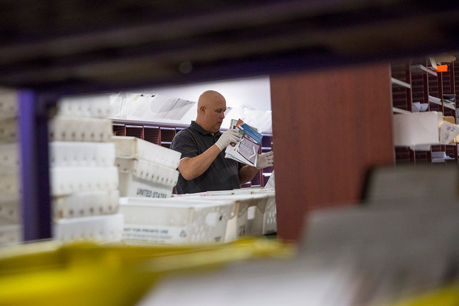 7:30 a.m. — Bob Smith sorts mail at the Harvard Mail Service Center in Allston. He and several other postal workers sing along to the radio as they prepare the day's mail for delivery.