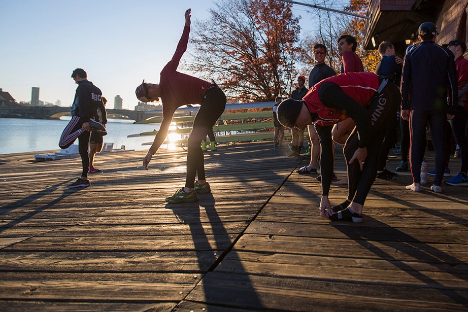 7:20 a.m. — Members of the men's rowing team stretch before an exhibition race between the lightweight and heavyweight teams as an alternative to their typical morning workout.