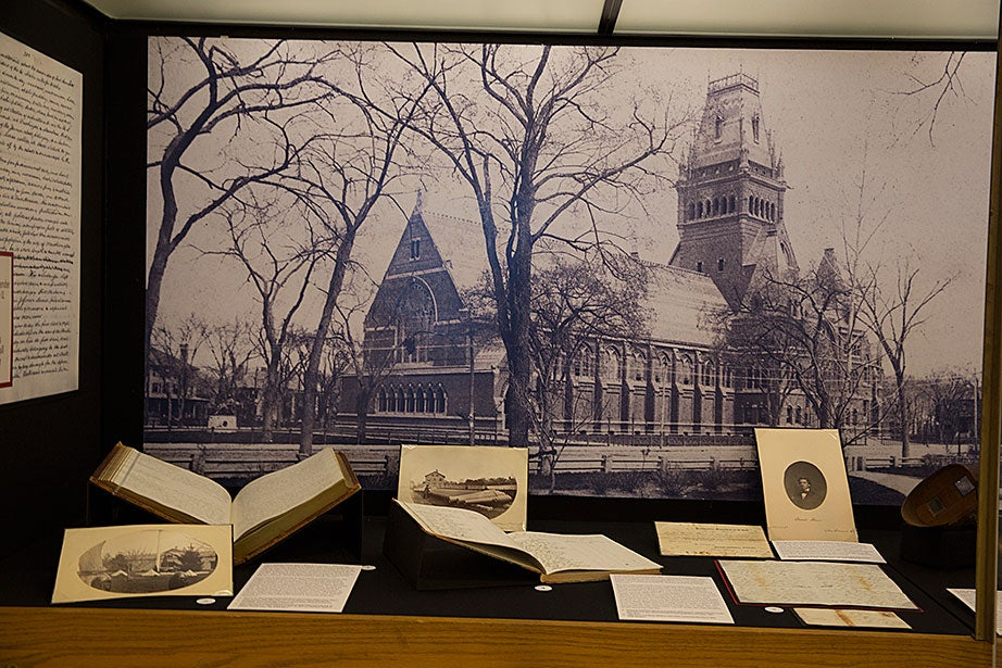 Photographs and letters from Harvard students, alumni, and administrators are arrayed in front of an 1888 photograph of Memorial Hall. Among the items on display are photographs of cannons and ammunition held at the Cambridge Arsenal, which Harvard students rushed to protect when the Civil War began.