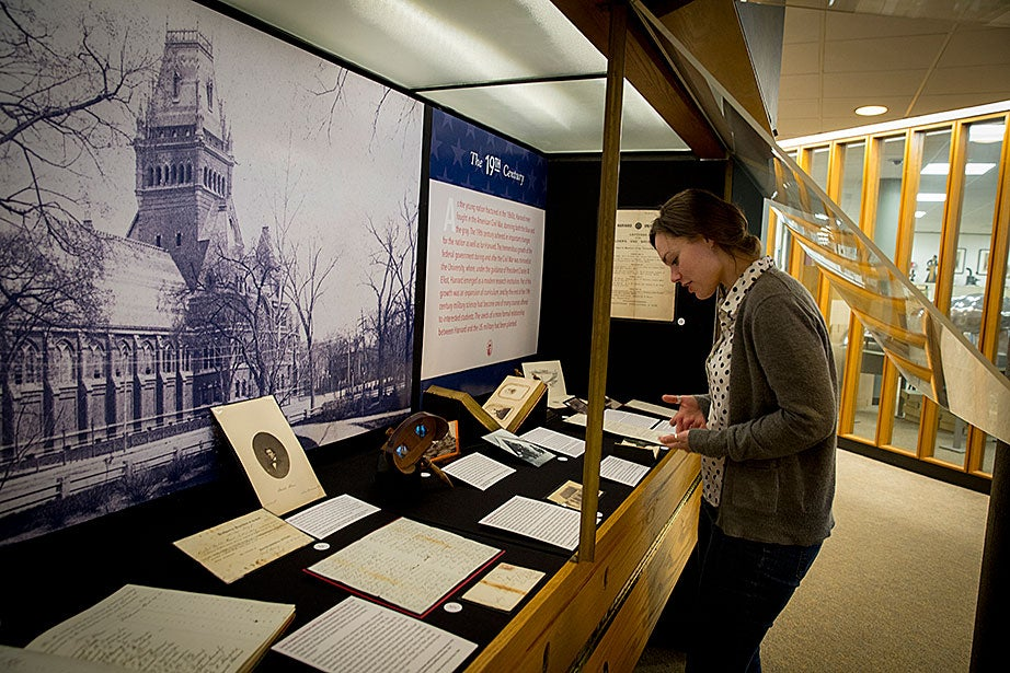 Emily Atkins, a survey archivist at Harvard, looks over some of the memorabilia on display at Pusey Library.