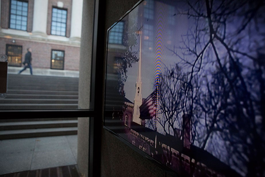 "In the entrance to Pusey Library, across from Widener Library, the American flag and steeple of Memorial Church are shown in ""Harvard Goes to War,"" a 1942 film that documents Harvard's contributions to the war effort during World War II."