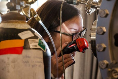 An attendee at the Conference for Undergraduate Women in Physics examines equipment in the lab of Michael J. Aziz, the Gene and Tracy Sykes Professor of Materials and Energy Technologies.