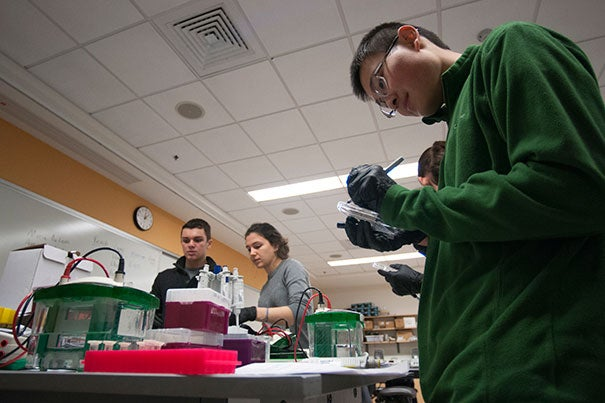 "From the right, the freshman students William Gao, Irla Belli and Dylan Rice conduct an experiment to study yeast cells during the Lab Session ""Genetics of Organelle Function in Budding Yeast"" guided by the instructor James Martenson, a Post-Doctoral Fellow in Molecular and Cellular Biology, in the Northwest Building Labs. Photo by Silvia Mazzocchin"