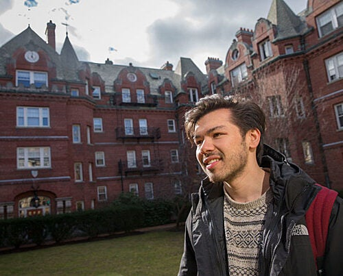 Sebastian Reyes '19, seen in the Adams House courtyard, reflects on the paradox of feeling at home both in Cambridge and his native Orange County, Calif.
